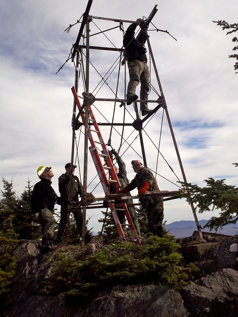 Several Maine Forest Service employees dismantle the historic fire tower on Big Moose Mountain in Greenville.