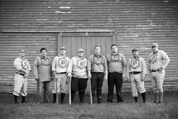 Members of the Dirigo vintage base ball team pose near a barn in New Gloucester. Vintage games, like games in the old days, are often played in farm fields.