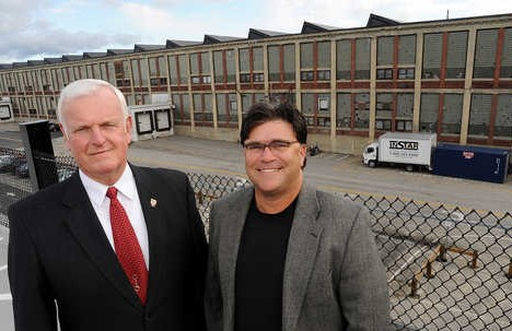 The new spokesman for the Lewiston casino project, Lewiston Mayor Larry Gilbert (left) and Ron Chicoine, the principal partner in the project, stand on  the top level of the new parking garage that they hope will someday be filled with the cars of people visiting a casino built in the Bates Mill (background).