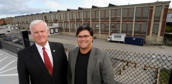 The new spokesman for the Lewiston casino project, Lewiston Mayor Larry Gilbert (left), and Ron Chicoine, the principal partner in the project, stand recently on the top level of the new parking garage that they hope will someday be filled with the cars of people visiting a casino built in the Bates Mill (background).