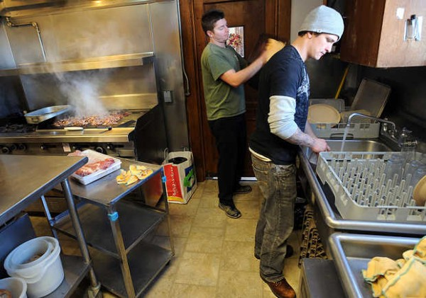 Nathan Brewer, right, and Dan Bell work in the kitchen while helping the cook prepare lunch for 32 residents at St. Francis Recovery Center in Auburn. Residents share chores throughout the home and on this particular day, Brewer and Bell chose to be kitchen aides.