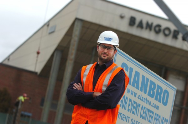 Joe Campbell, a project engineer for Cianbro at the Bangor Events Center contruction site, stands in front of the site and the Bangor Auditorium where he played many basketball games as a team standout for Bangor High School before graduating in 2001.