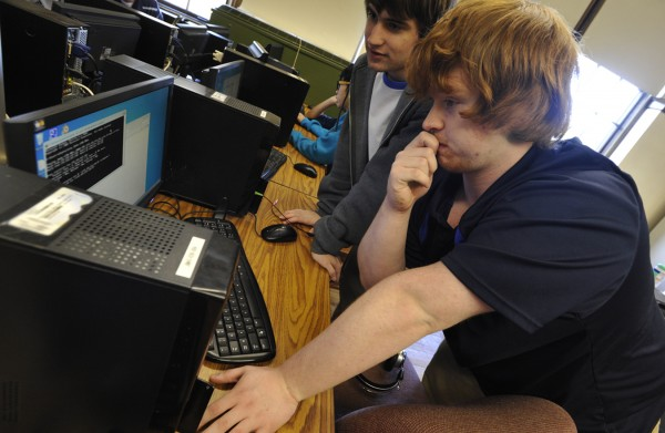 John Bapst seniors Ryan Bouchard and Carl Astbury, right, set up a computer for a classmate  before it was used  to go over a cyber defense vulnerabilty checklist during Thursday afternoon's practice session at the high school for an upcoming national cyber security competition.
