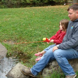 Kaitlyn Dyment, 4, of Corinna, was among the children fishing Saturday during the Hooked On Fishing event held in Dover-Foxcroft sponsored by the local Kiwanis Club. With Kaitlyn is her father, Brian Dyment, also of Corinna.