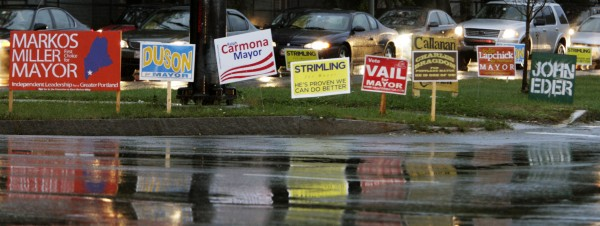 In this Oct. 19, 2011 photo, vehicles pass a multitude of signs representing some of the mayoral candidates in Portland, Maine, at dusk.