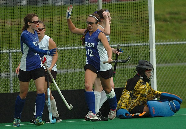 Belfast's Kelsey Grass (left) looks to high-five teammate Kendra Kirby (center) after Kirby scored the first goal of Saturday's Eastern Maine Class B semifinal field hockey game against John Bapst at the University of Maine in Orono.