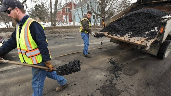 Bangor Public Works employees fill potholes in Bangor. Mainers can now report problems in their neighborhoods, such as potholes, on the BDN website.