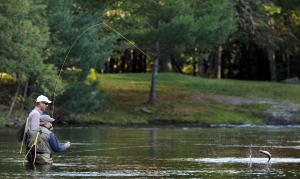 A landlocked salmon makes a jump as Mark Gregory of Dedham and Jeff Kane of Bangor team up to land the fish in the Cable Pool.