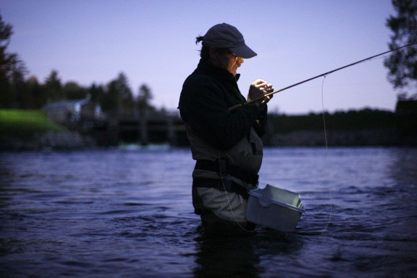 Joel Anderson of Auburn ties on a fly by the light of a headlamp under his hat as he fishes the Dam Pool at dawn.
