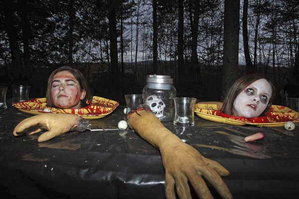 Meghan Hebert (left) and Kayla Doughty display their table manners in one of about 40 exhibits that are part of the Linneus Haunted Hayride.