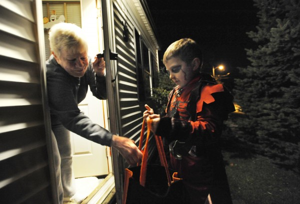 Amanda Hosmer treats 7-year-old Damien Greene of Brewer to the sweet stuff as he and his stepdad, Peter Merchant (not pictured,) made their way along Silk Street in Brewer on Halloween night. Damien said he was dressed as a demon