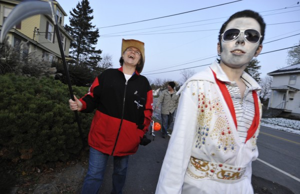 In the guise of &quotElvis,&quot Ian Johnson, 12, of Holden, his aunt Edner Fago (left) of Brewer and other family members made their way along Washington Street in Brewer in quest of sugar products on Halloween night.