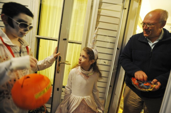 In the guise of &quotElvis,&quot Ian Johnson, 12, of Holden, and &quotunicorn&quot Justine Wyman, 9, of Holden, talk with candy donor Brian Fogg while trick-or-treating on Holyoke Street in Brewer with other family members Monday night, Oct. 31, 2011.