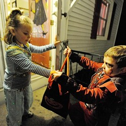 Living up to her princess persona, Maddison Pierce, 5, bestows candy upon Damien Greene, 7, of Brewer (aka a demon) as he and his stepfather, Peter Merchant of Brewer, made their way along Jefferson Street in Brewer Monday on Halloween night.