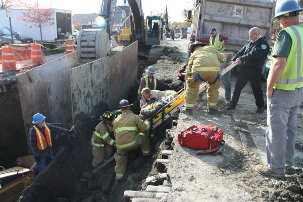 Rockland Fire Department personnel work to remove an unidentified man from debris after the pavement gave way at a construction site on Limerock Street in Rockland on Wednesday, Oct. 26, 2011.