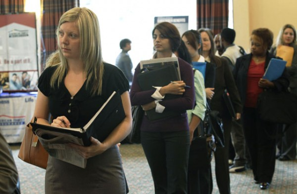 In this Sept. 14, 2011 file photo, Annelie Ingvarsson, left, waits in line to talk to potential employers during a National Career Fairs job fair, in Bellevue, Wash.
