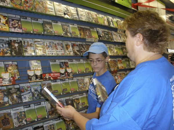 Sam Alexander happily makes selections of video games at GameStop in Bangor as he enjoying having his shopping spree wish granted by Make-A-Wish Maine Foundation of Maine.