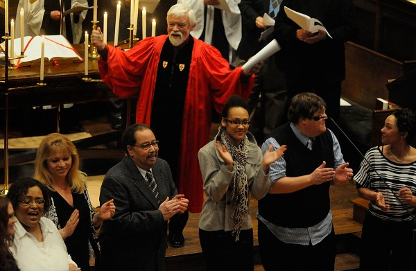 Arms outstretched, the Rev. James L. Haddix asks the congregation to join the multichurch choir in song during a January &quotService of Light&quot in remembrance of the Rev. Martin Luther King Jr. at All Souls Congregational Church in Bangor.