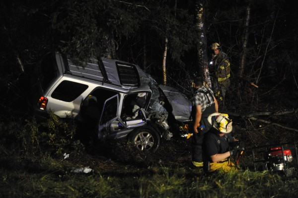 Walking around the tree line, Medway firefighters look over the heavily damaged SUV in which the driver, Elizabeth Gould of Millinocket, was killed near mile marker 238 on I-95 northbound several miles south of the Medway exit  on Thursday evening, Oct. 20, 2011.