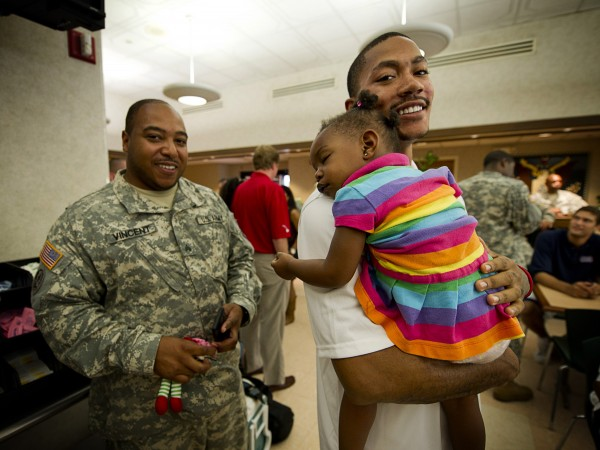 Derrick Rose of the Chicago Bulls holds U.S. Army  Sgt. Vincent's daughter at Schofield barracks near Honolulu on Monday, Oct. 24, 2011. Rose, in Hawaii this week visiting military personnel as part of the Hoops for Troops USO Tour, undoubtedly will earn a lot more when he becomes a free agent at the end of his four-year, $22.5 million contract, depending on the new NBA labor agreement, of course.