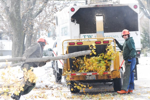 Tristan Graf and Bob Morong of T.W. Enterprises Inc. work on Winding Way in Portland on Oct. 30, feeding branches damaged in the October storm into a chipper.