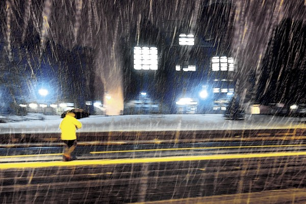 A pedestrian walks in a burst of moderate snow in front of the Vernon, Conn., Town Hall during the first snowfall of the season Thursday, Oct. 27, 2011. More snow is forecast in the Northeast on Saturday.