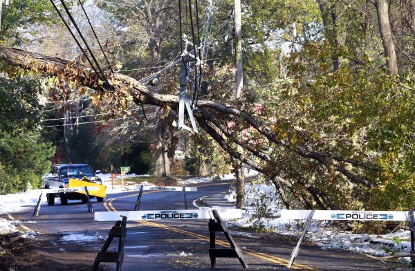 A snowplow truck backs away from a street blocked by downed power lines in North Andover, Mass., Monday, Oct. 31, 2011, in the wake of a storm which dumped as much as 30 inches of wet, heavy snow that snapped trees and power lines, and caused widespread power failures.