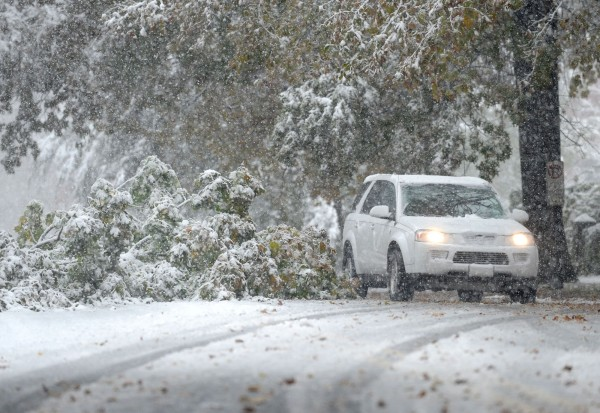 A car drives around a fallen tree on Market Street as heavy snow continues to fall bringing down trees and branches throughout the region, Saturday, Oct. 29, 2011 in Bethlehem, Pa.