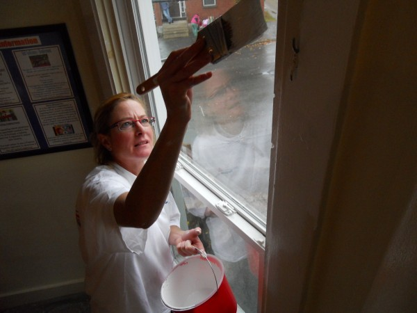 Volunteer Heidi Fenwick of South Portland-based C.H. Rosengren Painting and Repairs gives a window frame at Portland's family shelter a fresh coat of Super White paint, donated by Benjamin Moore Paints.