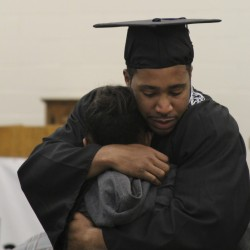 Inmate Edwin Devaughn Keys, who earned his associate degree Wednesday from an in-prison program, hugged his 11-year-old daughter Kapri Keys who cried after her dad was handed his diploma in Maine State Prison.