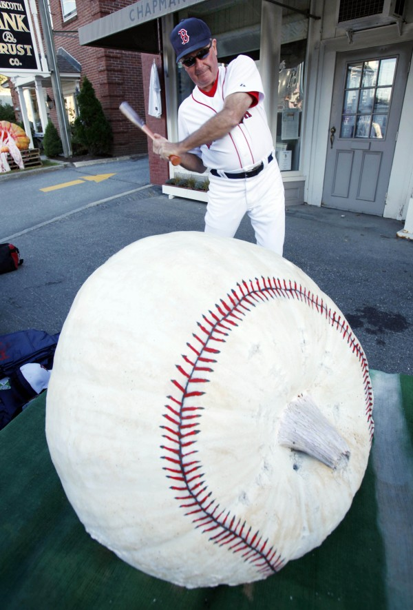 Bud Elwin, 72, of Walpole, does his Ted Williams pose next to a giant painted pumpkin at the Damariscotta Pumpkinfest. Elwin was raffling off baseball memorabilia to raise money for the Healthy Kids program.