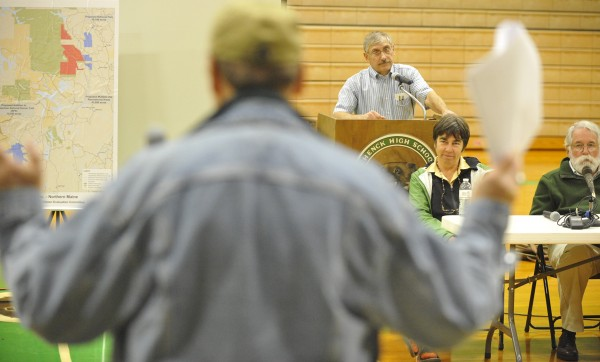 Stu Kallgren (foreground) of West Enflield, shrugs as he refers to Quimby's recent Forbes interview as he addresses Roxanne Quimby, Bob McIntosh (far right, a retired senior National Park Service official) and other participants in Thursday evening's feasibility study meeting at Schenck High School in East Millinocket. Moderating the public meeting was Schenck principal John W. Farrington (standing behind lectern).