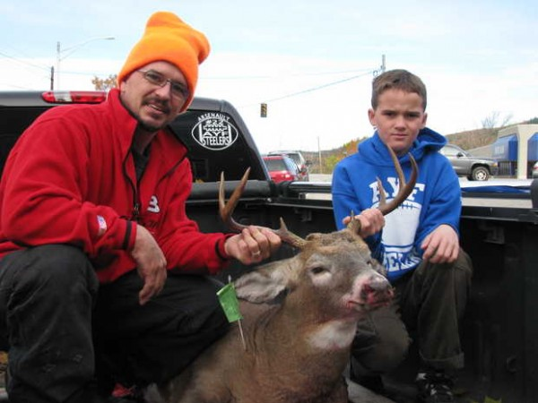 &quotCussy&quot Arsenault and his son, Damien, 10, both of Rumford, proudly display dad's first deer. The 8-point buck weighed 193½ pounds on the scale at the Rumford Fire Department tagging station Saturday, the opening day of Maine's regular firearms deer season.