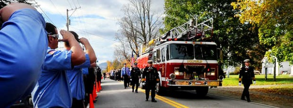 Firefighters from Turner salute the ladder truck carrying Dani Ranger's urn before her memorial service Friday at Dirigo High School in Dixfield.