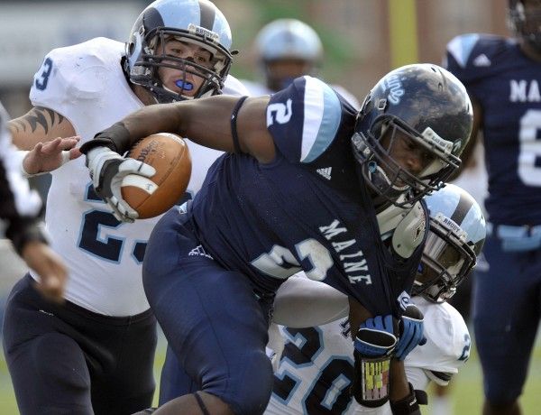 Maine running back Pushaun Brown (2) is pulled down by Rhode Island's Michael Okunfolami (20) and Doug Johnson (23) during the first half of an NCAA football game in Orono, Maine, Saturday, Oct. 15, 2011.