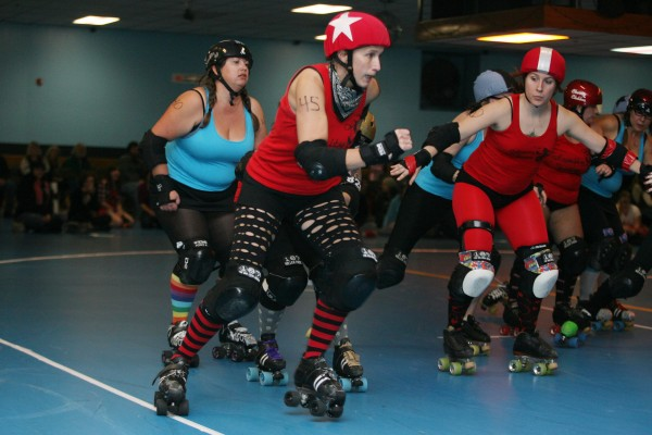 The Calamity Janes' T-Storm (center) plays the position of jammer as teammate The Rehabiliskater (right) tries to guard her during a Maine Roller Derby bout Saturday.