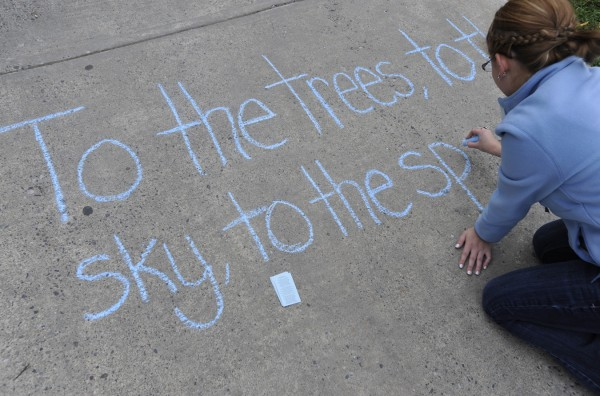 Student Amanda Mayette of Readfield writes a verse of the University of Maine's &quotMaine Stein Song&quot on the sidewalk to the Folger Library on Wednesday afternoon after joining fellow honor society members in singing that song there.