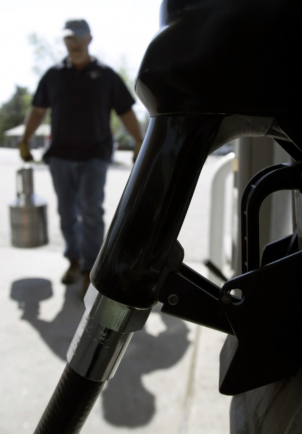 In this May 4, 2010 photo, Carlton Blanche, a state consumer protection inspector, carries a calibrated test measuring can by a fuel pump at a gas station in Maine.  The state has shut down gas pumps at several locations because the pumps were shortchanging motorists.