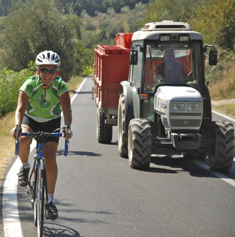 Cyclist Christine Chasse powers up a Tuscan hillside alongside a farmer hauling freshly harvested grapes.