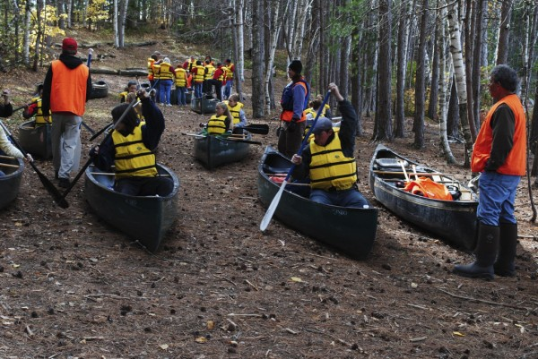Students enrolled in the Maine Outdoor Education Program learn the draw stroke from instructors on dry land before entering Upper Togue Pond for a morning paddle last Tuesday.