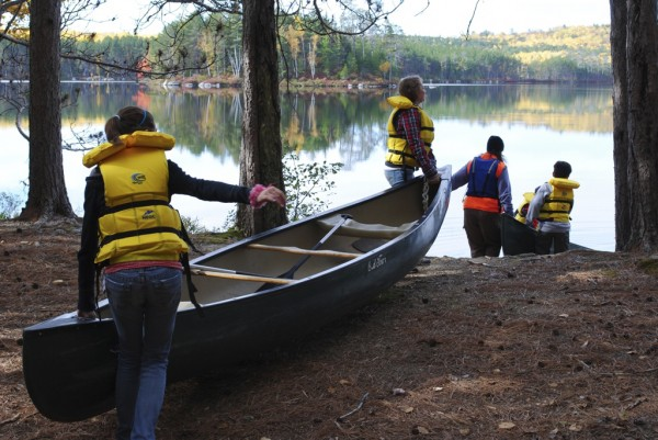Students in the Maine Outdoor Education Program carry their canoes down to the shore of Upper Togue Pond. BRAD VILES PHOTO