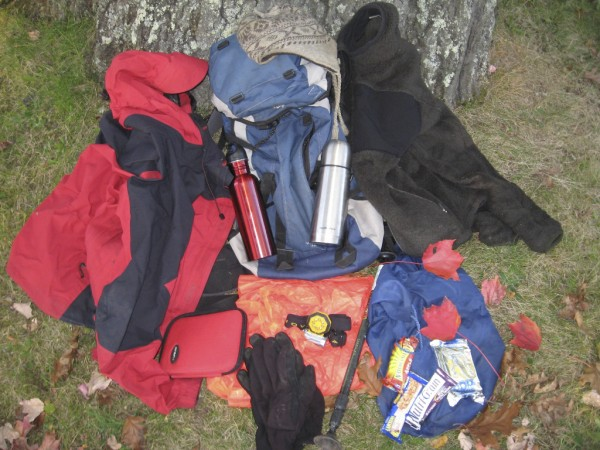 When hiking in fall, pack these items for comfort, safety and varying conditions. Starting at the top of the pack and going clockwise: A fleece or wool cap, a fleece insulating layer, snacks on the stuff sack, trekking pole, headlamp, fleece gloves, blaze orange poncho, first aid kit, rainshell which doubles as a wind shell. On the pack, a steel water bottle and thermos.