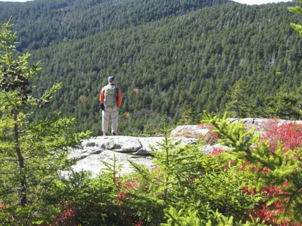 A hiker on the trail to Mansell Mountain in Acadia takes in the fall view.