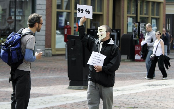 Benjamin Hider of Portland wears a mask and holds up a sign Monday. The group Occupy Maine has joined in solidarity with Wall Street protesters in New York and across the country who are demonstrating against corporate greed and other issues.