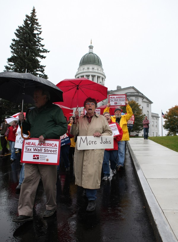 Protesters march from the State House to the Federal Building during a rally to encourage Congress to pass legislation to create jobs and enact a financial transaction tax on Thursday, Oct. 13, 2011, in Augusta.