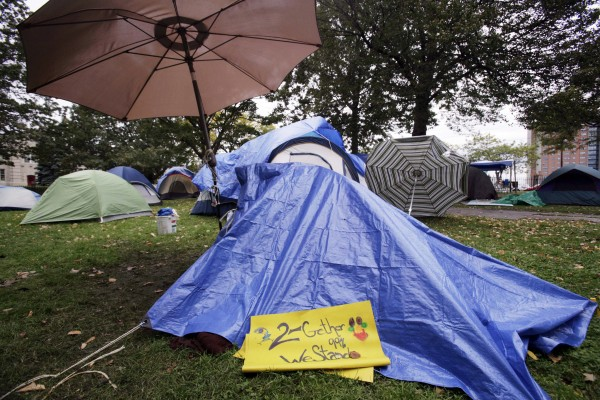 A sign that reads &quot2-Gether 99% We Stand&quot lies on one of the tents that belongs to a group that calls itself Occupy Maine in a park in Portland on Wednesday, Oct. 19, 2011.
