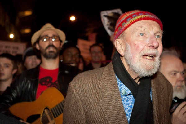 Activist musician Pete Seeger, 92, left, marches with nearly a thousand demonstrators sympathetic to the Occupy Wall Street protests for a brief acoustic concert in Columbus Circle, Friday, Oct. 21, 2011, in New York. The demonstrators marched down Broadway singing &quotThis Little Light of Mine&quot and other folk and gospel songs while ad-libbing lines about corporate greed and social justice.