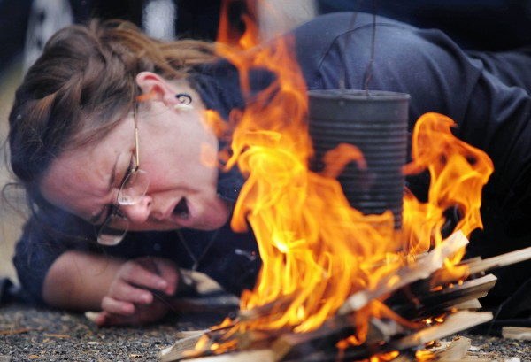 At risk of singeing her eyebrows, Laurette Russell of New Gloucester blows on her fire in a race to get a can of water to boil over in the tea boil contest during the Woodsman's Filed day at the Fryeburg Fair.