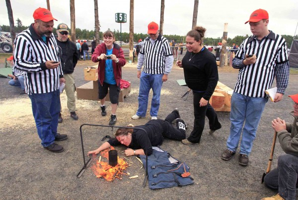 Laurette Russell of New Gloucester blows on her fire in a race to get a can of soapy water to boil in the tea boil contest. Referees keep stand by with stopwatches. Competitions are based on traditional tasks performed by loggers in days gone by.