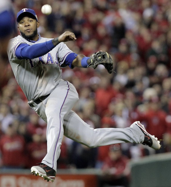 Texas Rangers' Elvis Andrus makes a play on a ball hit by St. Louis Cardinals' Lance Berkman during the seventh inning of Game 7 of baseball's World Series Friday, Oct. 28, 2011, in St. Louis. Berkman beat the throw.